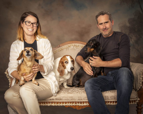 A picture of Christy, Mike, and the pups on a couch